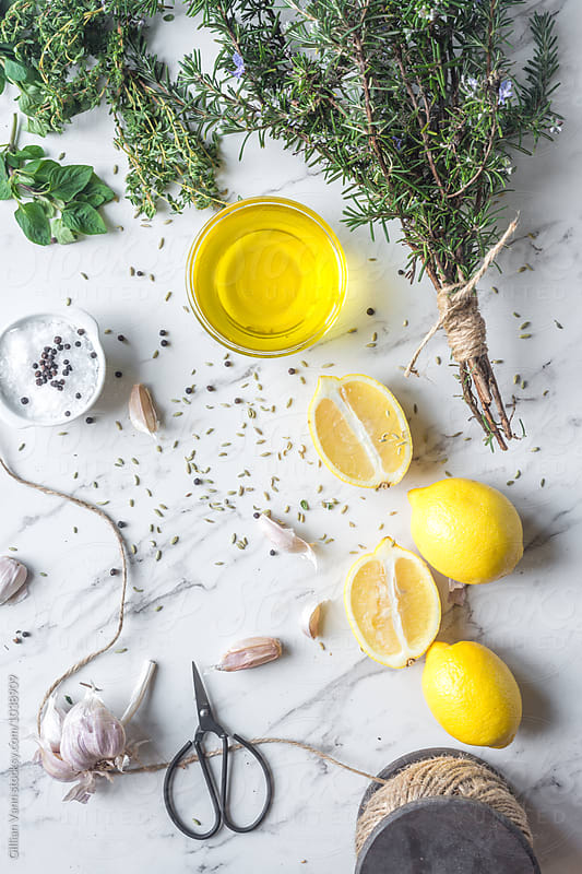 ingredients for a greek flavoured marinade, including lemon, olive oil, rosemary, oregano, thyme, garlic, fennel, salt and pepper by Gillian Vann for Stocksy United