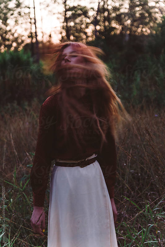 Young girl flipping her hair in field by Image Supply Co for Stocksy United
