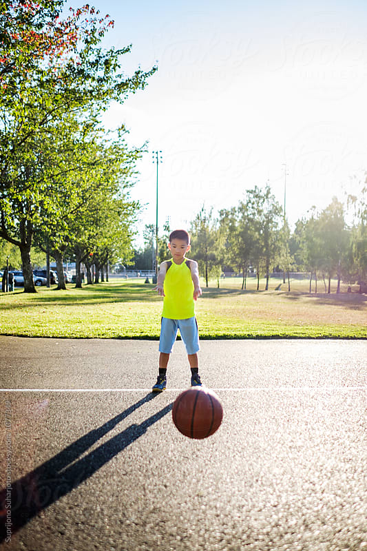 Asian kid passing a basketball in an outdoor basketball court by Suprijono Suharjoto for Stocksy United