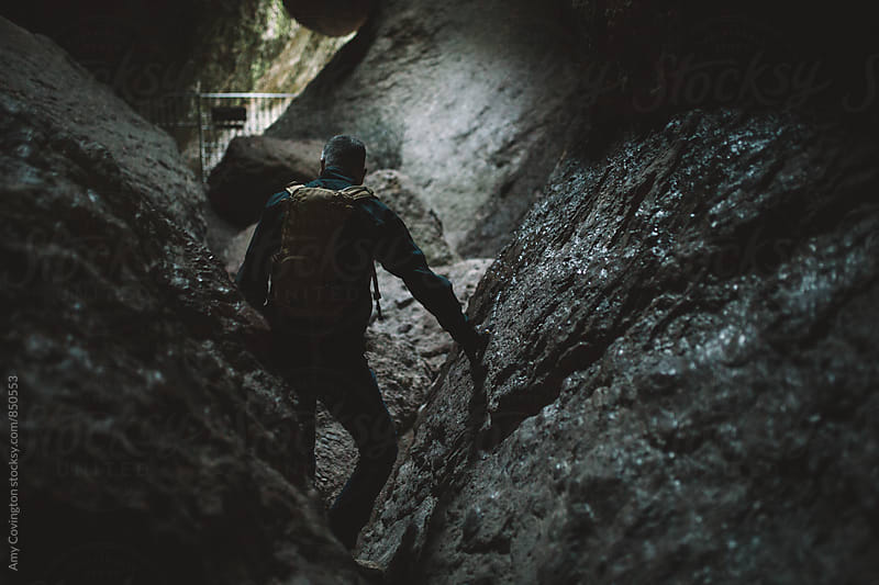 A man hiking in a cave by Amy Covington for Stocksy United