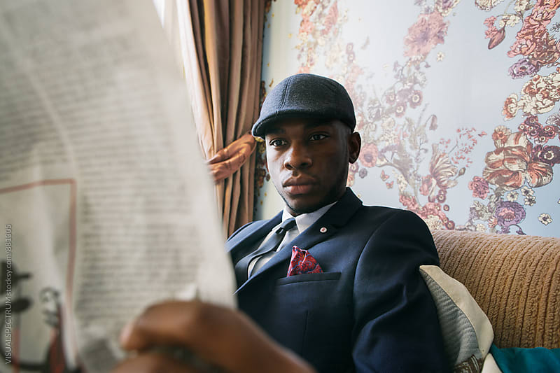 Close Up of Elegant Black Man Reading Newspaper in Colorful Living Room by Julien L. Balmer for Stocksy United