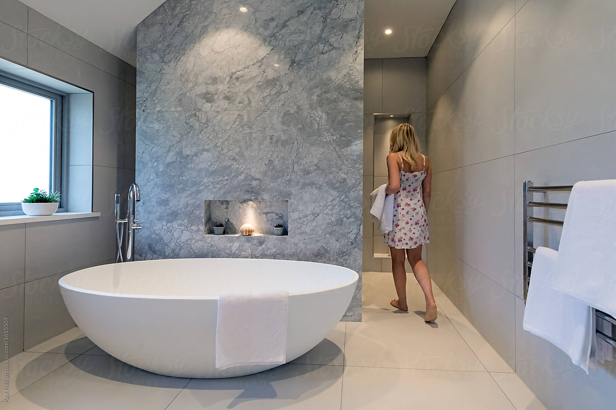 Contemporary Bathroom With White Oval Bath And Marble Background. Woman  Walking Into The Shower Behind