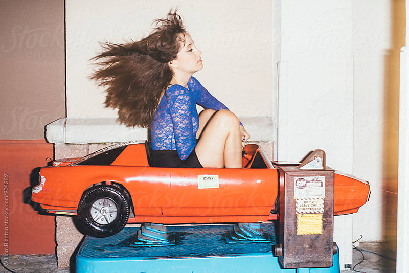 Woman fashion model posing and riding coin operated car ride at night by William Blanton for Stocksy United