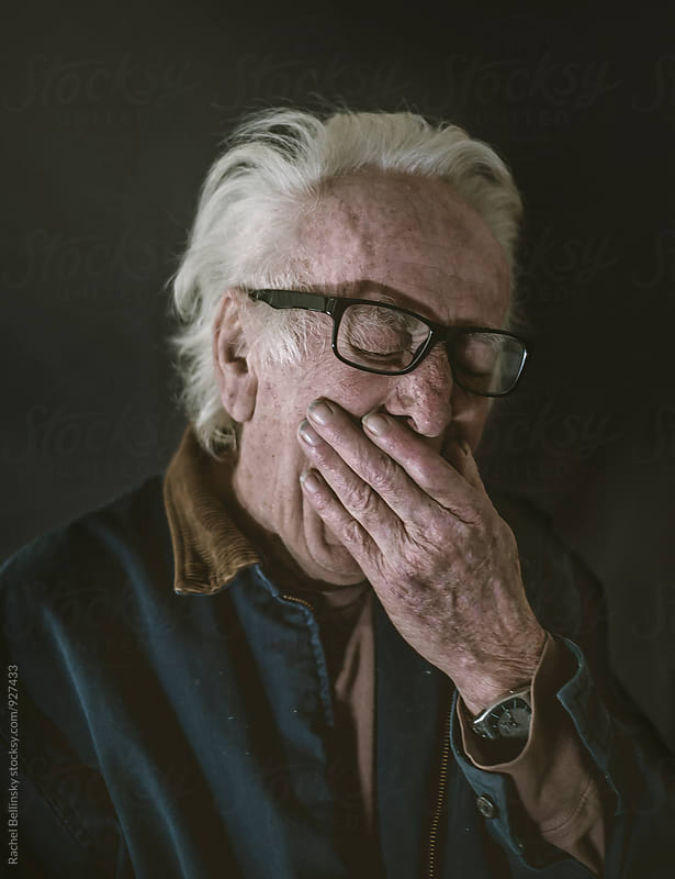 Portrait of an older man yawning by Rachel Bellinsky for Stocksy United