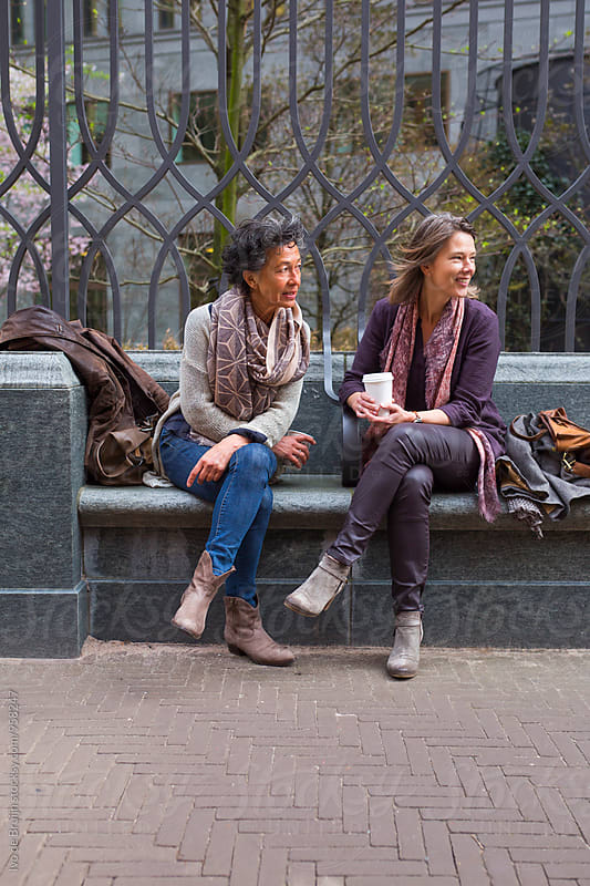 Two women drinking coffee together outside, having fun and talking by Ivo de Bruijn for Stocksy United