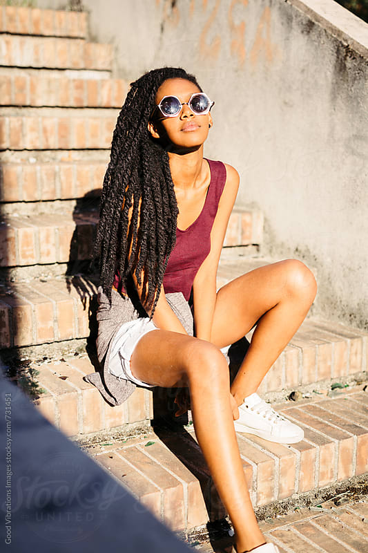 African Woman sitting on Steps by Good Vibrations Images for Stocksy United