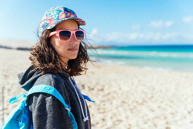 Stylish young woman wearing a colourful cap, pink sunglasses and a blue handbag, in a deserted beach by Inuk Studio for Stocksy United