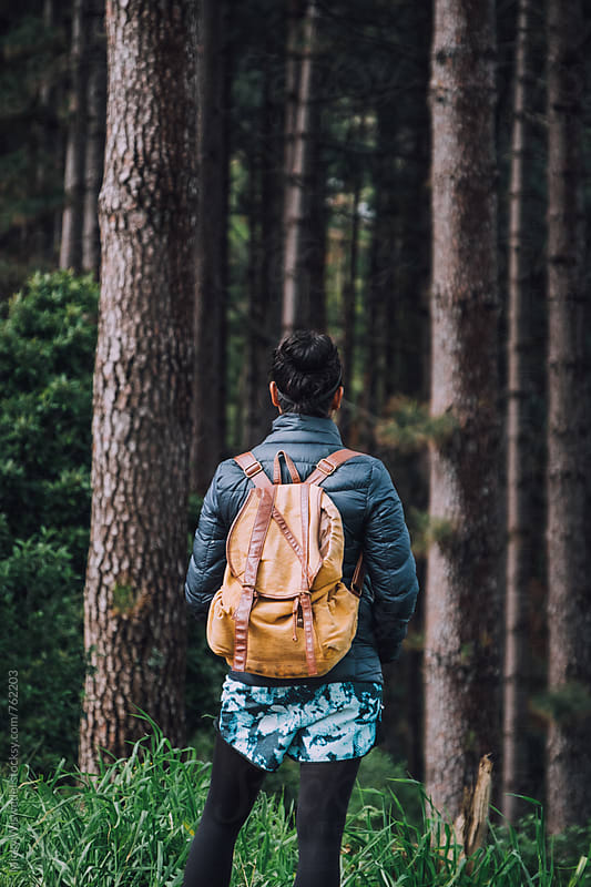 Woman with a backpack hiking in a forest by Micky Wiswedel for Stocksy United