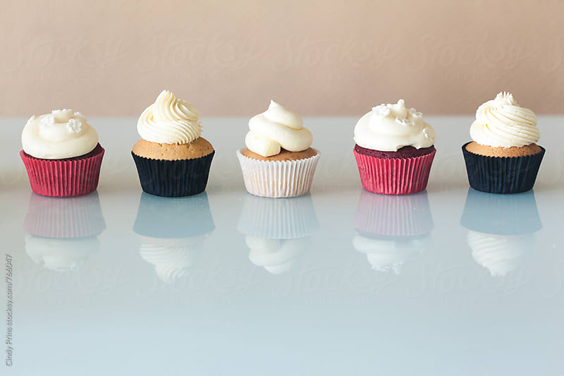 A row of six cupcakes on a glass table with reflection by Cindy Prins for Stocksy United