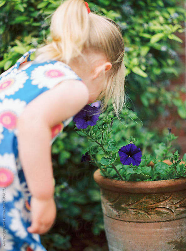 Young girl smelling flowers by Andrew Spencer for Stocksy United