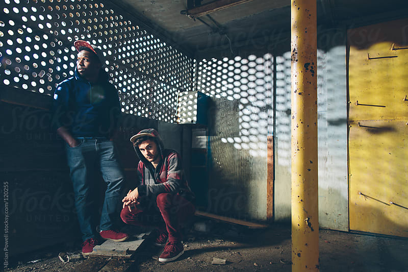 two young guys hiding in a warehouse by Brian Powell for Stocksy United