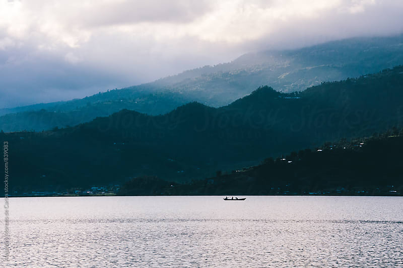 Boat on a lake with light rays and mountains. Travel image in Pokhara, Nepal by Alejandro Moreno de Carlos for Stocksy United