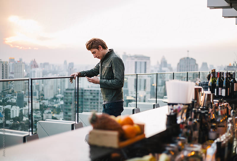 Man looking at the city from a rooftop bar by Jovo Jovanovic for Stocksy United
