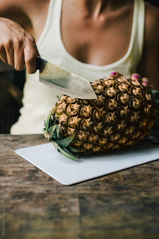 Woman Cutting Pineapple by Marija Savic for Stocksy United
