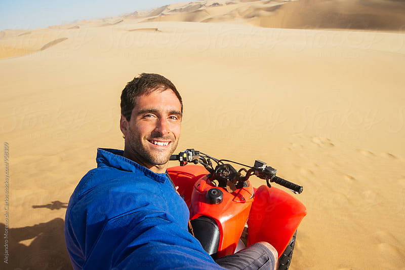 Happy man taking selfie on quad bike by Alejandro Moreno de Carlos for Stocksy United