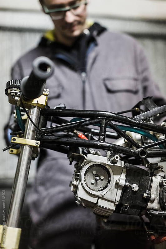 Mechanic works on mini motorbike by Mauro Grigollo for Stocksy United