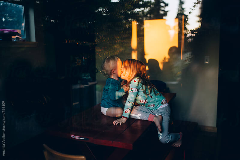 Young Siblings smile and kiss on the kitchen table as seen from outside by Amanda Voelker for Stocksy United