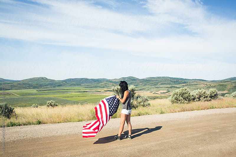 Young Woman in Field with American Flag by MEGHAN PINSONNEAULT for Stocksy United