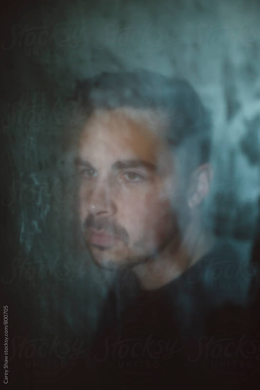 Portrait of man through diffused glass by Carey Shaw for Stocksy United