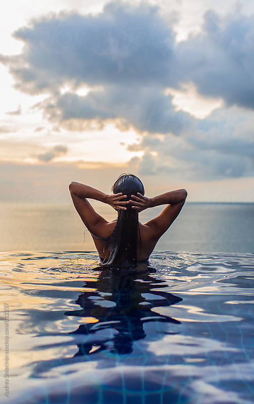Woman at the edge of swimming pool with sea horizon and sky in background during sunset. by Audrey Shtecinjo for Stocksy United