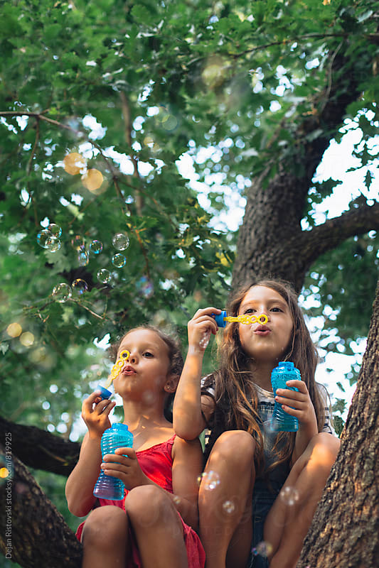 Girls on a tree blowing bubbles. by Dejan Ristovski for Stocksy United