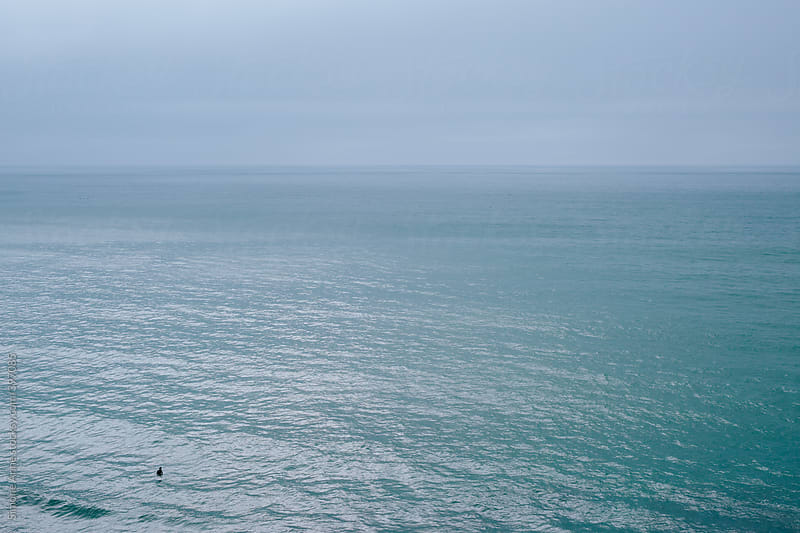 Surfer alone in large stormy ocean by Simone Anne for Stocksy United