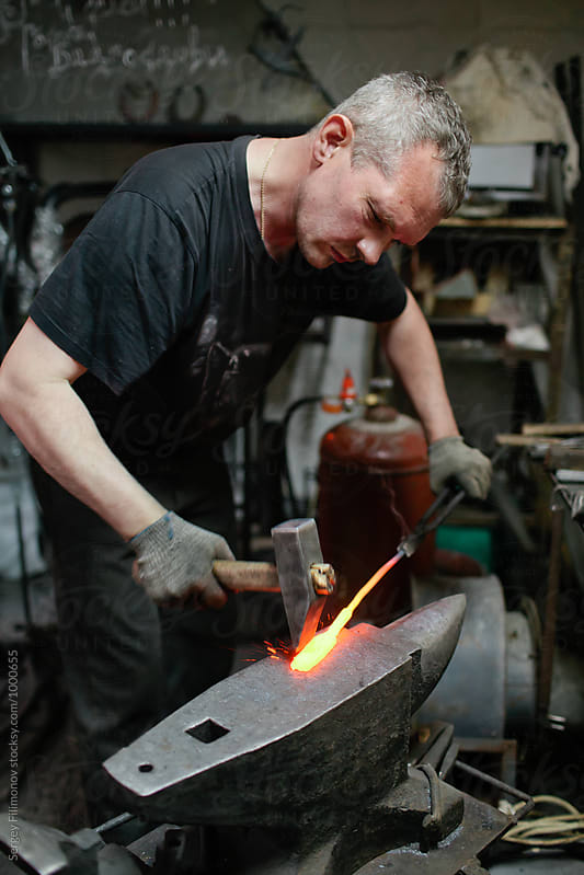 Caucasian adult male blacksmith working with metal  by Sergey Filimonov for Stocksy United