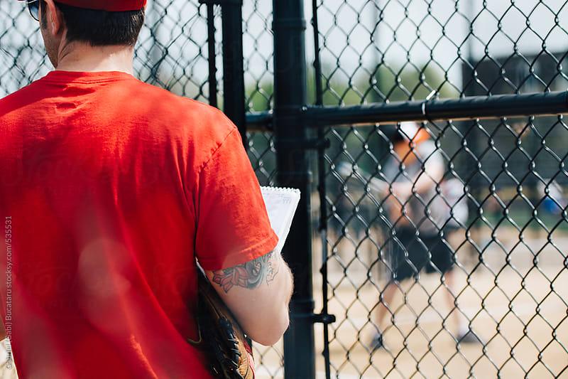 Baseball coach with red shirt at a junior baseball game by Gabriel (Gabi) Bucataru for Stocksy United