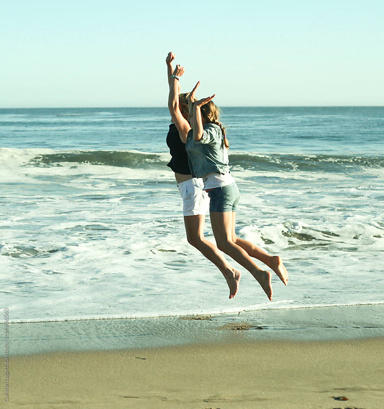 Mother and daughter jumping happily at the beach by Carolyn Lagattuta for Stocksy United