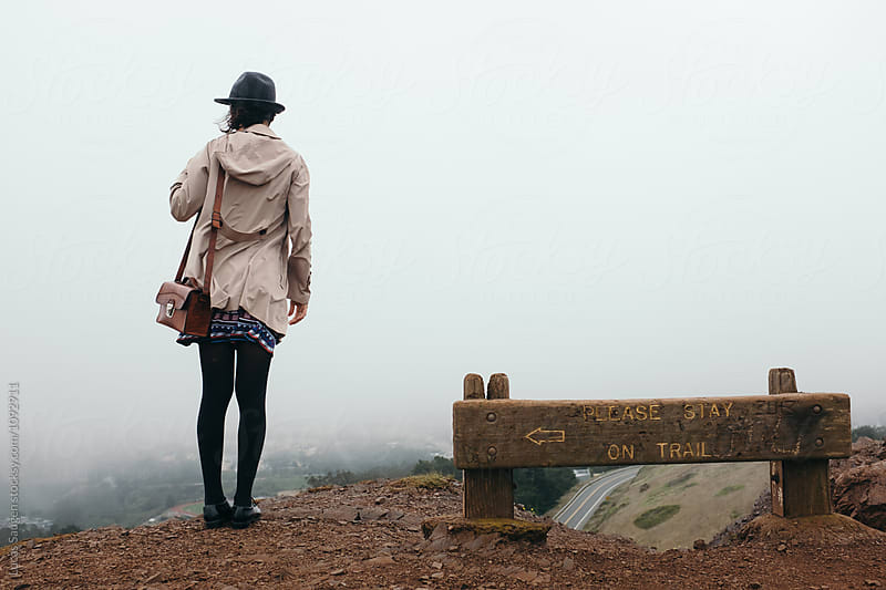 Unrecognizable woman in hat and coat against of foggy San Francisco by Lucas Saugen for Stocksy United