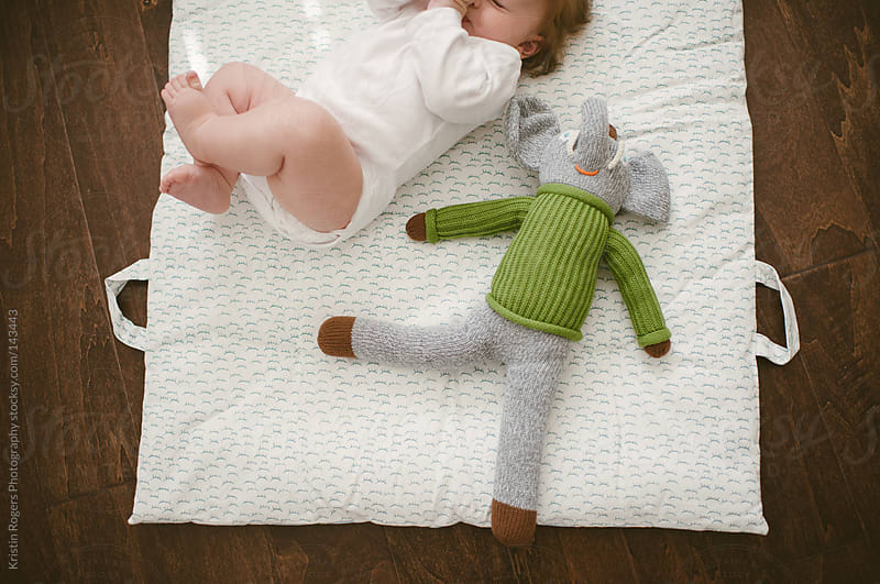 baby laying on blanket with toy elephant by Kristin Rogers Photography for Stocksy United