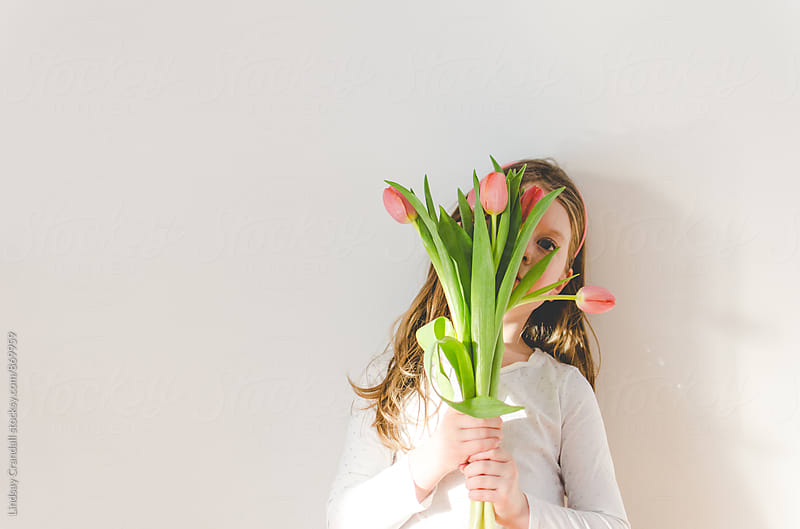 Young child holding tulips in front of her face by Lindsay Crandall for Stocksy United