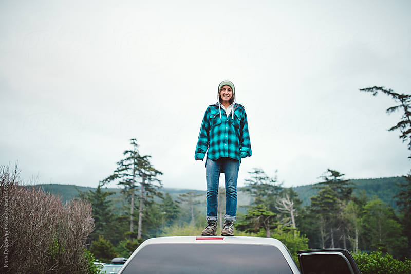 Young woman standing on top of truck in woods by Kate Daigneault for Stocksy United