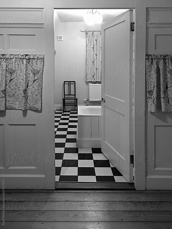 Retro bathroom with checkered floor. by Paul Phillips for Stocksy United
