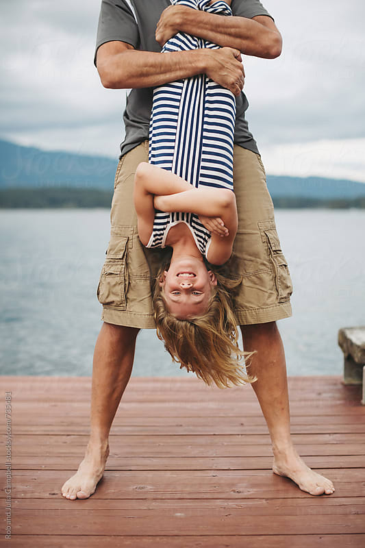 Young girl hanging upside down laughing - on the dock at the lake by Rob and Julia Campbell for Stocksy United