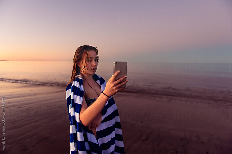 Girl taking photos on a phone camera at the beach after sunset by Angela Lumsden for Stocksy United