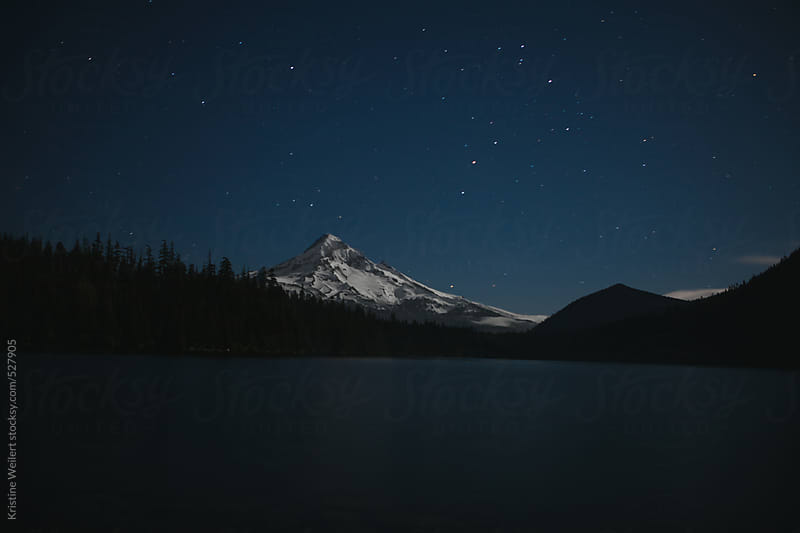 Snow covered mountain at night with stars in the sky by Kristine Weilert for Stocksy United
