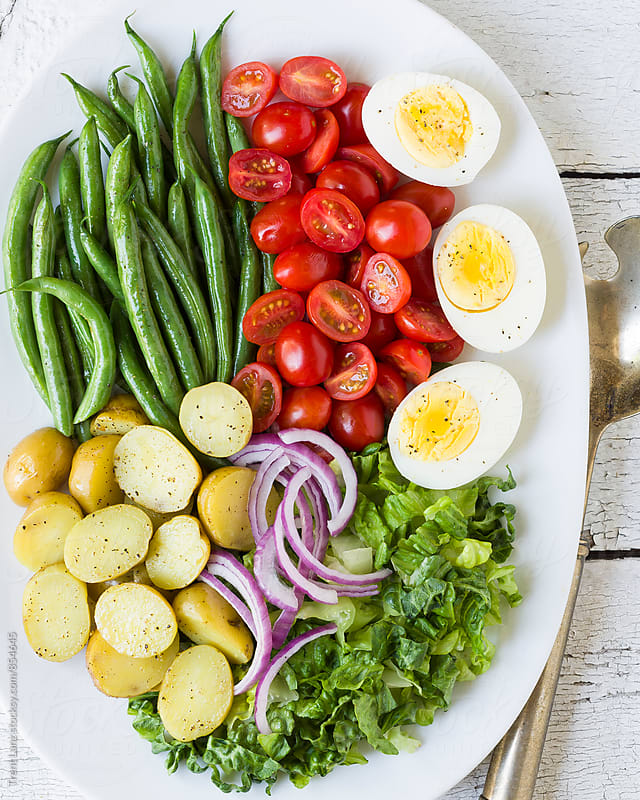 Homemade nicoise salad with different vegetables and boiled eggs on plate by Trent Lanz for Stocksy United