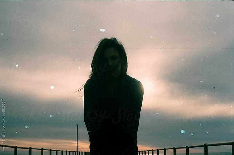A portrait of woman on the sunset made with expired film by Anna Malgina for Stocksy United