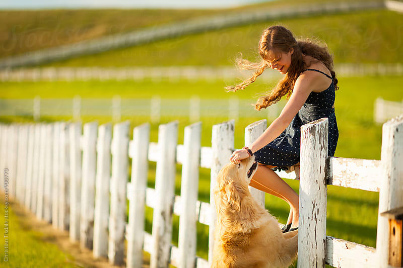 Girl sitting on white fence with golden retriever by Christian Tisdale for Stocksy United