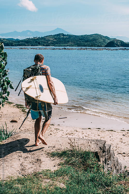 Surfer walking to the beach carrying white surfboard by Soren Egeberg for Stocksy United
