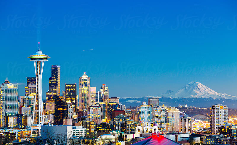 Characteristic horizontal view of downtown Seattle with Space Needle and Mount Rainier at sunset by Mihael Blikshteyn for Stocksy United