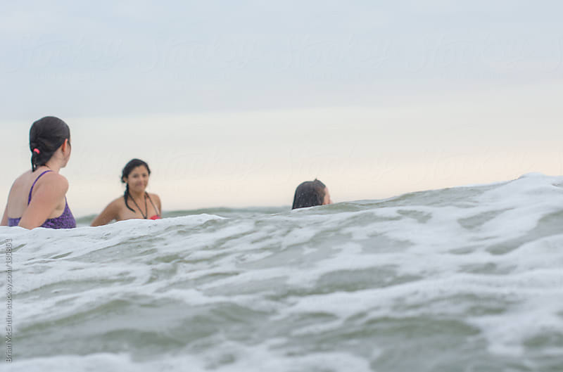 Female members of Family Swim in Atlantic Ocean Near Sunset by Brian McEntire for Stocksy United