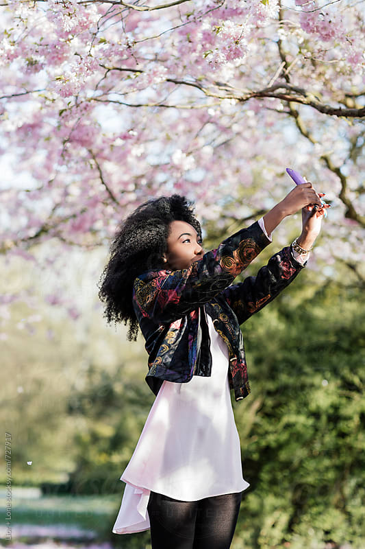 Young black woman photographing the cherry blossom outdoors by Lior + Lone for Stocksy United