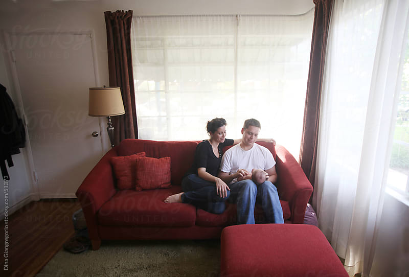 Couple on couch in living room holding newborn baby by Dina Giangregorio for Stocksy United