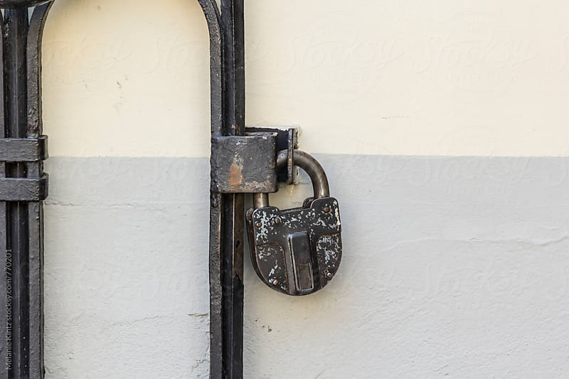 Padlock on a gate by Melanie Kintz for Stocksy United
