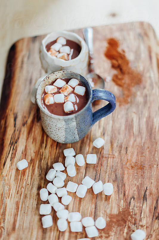 hot chocolate and marshmallow drink on wooden table by Treasures & Travels for Stocksy United