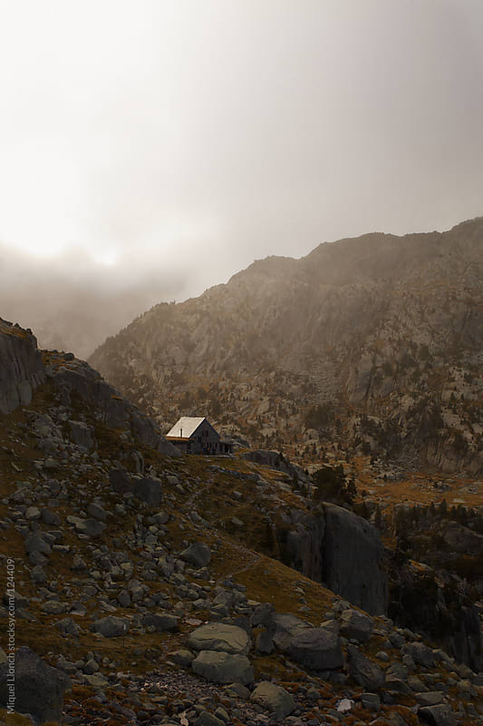 Mountain hut in a foggy day in the Pyrenees mountains by Miquel Llonch for Stocksy United