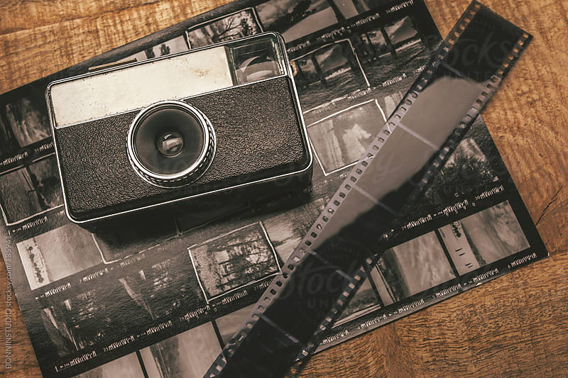 Old analog camera, film and contact sheet over wooden table. by BONNINSTUDIO for Stocksy United