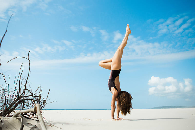 women in handstand with bent leg on empty beach  by Tahl Rinsky for Stocksy United